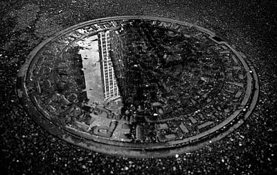 Surrealism Royalty-Free and Rights-Managed Images - Skyscraper Reflection in Manhole Cover by Mark Robert Davey