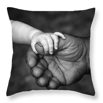 Babys Hand Holding On To Adult Hand Throw Pillow by Corey Hochachka