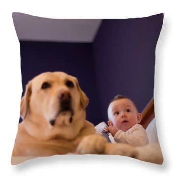 A Baby And Dog Sitting On A Bed Throw Pillow