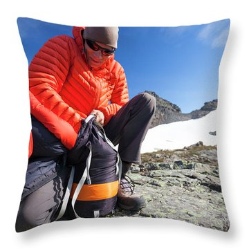 A Backpacker Stuffs His Sleeping Bag Throw Pillow