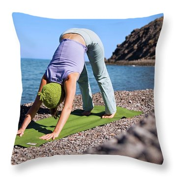 A Woman Practicing Yoga On A Pebble Throw Pillow