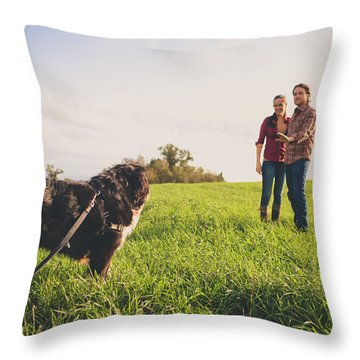 A Young Couple Instruct Their Bernese Throw Pillow
