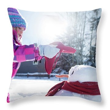 A Young Girl Building A Snowman Throw Pillow