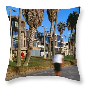 People Riding Bicycles Near A Beach Throw Pillow