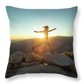 Person Leaping Along Rocks At Sunset Throw Pillow