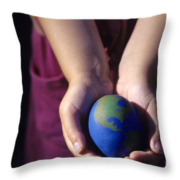 Young Girl Holding Earth Egg Throw Pillow by Jim Corwin