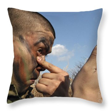 A Soldier Applying Face Paint Prior Throw Pillow by Stocktrek Images