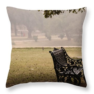 Throw Pillow featuring the photograph A Wrought Iron Black Metal Bench Under A Tree In The Qutub Minar Compound by Ashish Agarwal