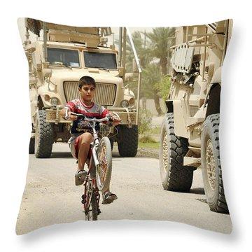 An Iraqi Boy Rides His Bike Past A U.s Throw Pillow by Stocktrek Images