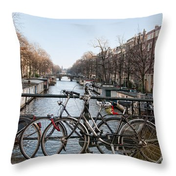 Throw Pillow featuring the digital art Bikes On The Canal In Amsterdam by Carol Ailles