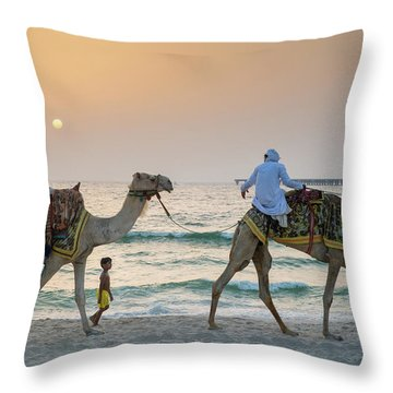 A Little Boy Stares In Amazement At A Camel Riding On Marina Beach In Dubai, United Arab Emirates Throw Pillow