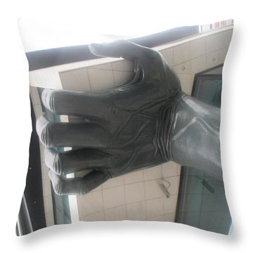 an arm holding a building in Lisbon Throw Pillow