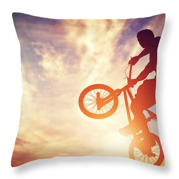 Man Riding A Bmx Bike Performing A Trick Against Sunset Sky Throw Pillow