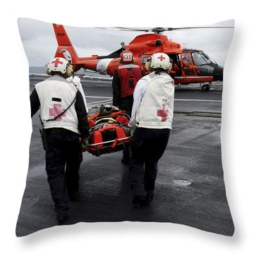 Personnel Carry An Injured Sailor Throw Pillow by Stocktrek Images