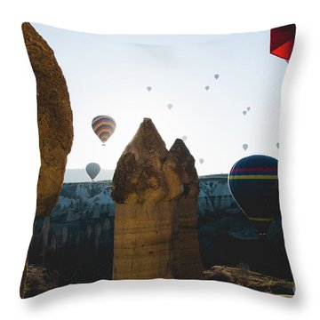 hot air balloons for tourists flying over rock formations at sunrise in the valley of Cappadocia. Throw Pillow
