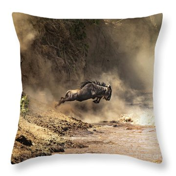 Wildebeest Leaps From The Bank Of The Mara River Throw Pillow