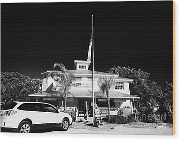 Raising The American Flag On A Flagpole Outside The Chamber Of Commerce Building In Key Largo Florid Wood Print by Joe Fox