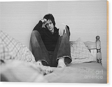 Young Dark Haired Teenage Man Sitting At The Far End Of His Bed In An Untidy Bedsit Bedroom Curled U Wood Print by Joe Fox