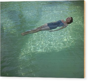 A Model Floating In A Swimming Pool By John Rawlings