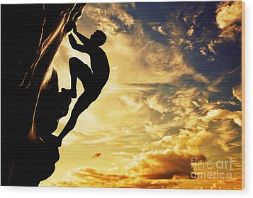 A Silhouette Of Man Free Climbing On Rock Mountain At Sunset Wood Print