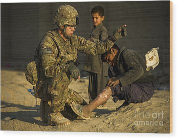 Airman Provides Medical Aid To A Local Wood Print by Stocktrek Images
