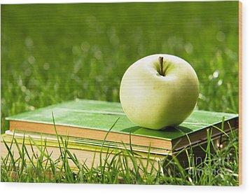 Apple On Pile Of Books On Grass Wood Print by Michal Bednarek