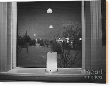 candle in the window looking out over snow covered scene in small rural village of Forget Saskatchew Wood Print by Joe Fox