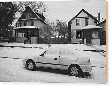 car covered in snow parked by the side of the street in front of residential homes caswell hill Sask Wood Print by Joe Fox