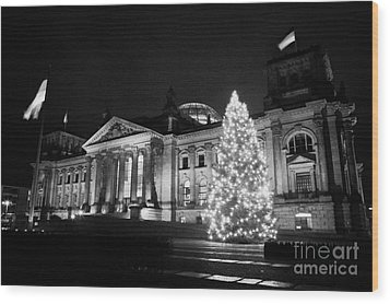 christmas tree and german flag flying fluttering on flagpole outside reichstag building Berlin Germany Wood Print by Joe Fox