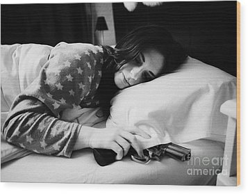 Early Twenties Woman With Hand On Handgun Under Pillow At Night In Bed In A Bedroom Wood Print by Joe Fox