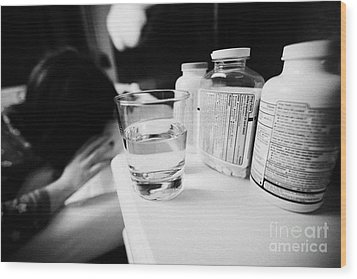 Glass Of Water And Bottles Of Pills On Bedside Table Of Early Twenties Woman Waking In Bed In A Bedr Wood Print by Joe Fox