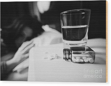 Glass Of Water And Bottles Of Sleeping Pills On Bedside Table Of Early Twenties Woman In Bed In A Be Wood Print by Joe Fox