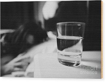 Glass Of Water On Bedside Table Of Early Twenties Woman In Bed In A Bedroom Wood Print by Joe Fox