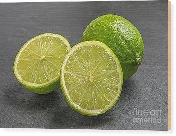 Limes On A Slate Plate Wood Print by Palatia Photo