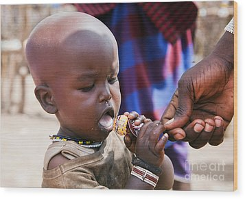 Maasai Child Trying To Eat A Lollipop In Tanzania Wood Print by Michal Bednarek
