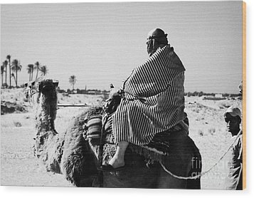 male tourist in desert clothing being led on the back of a camel into the sahara desert at Douz Tunisia Wood Print by Joe Fox