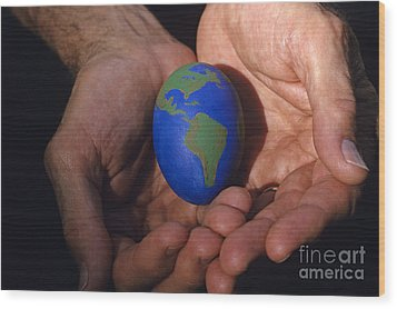 Man Holding Earth Egg Wood Print by Jim Corwin
