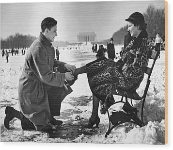 Man Lends A Helping Hand To Put On Skates Wood Print by Underwood Archives