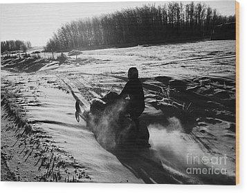 man on snowmobile crossing frozen fields in rural Forget canada Wood Print by Joe Fox