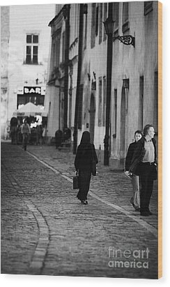nun with briefcase walking up cobblestone street Kanonicza past tourists in old town krakow Wood Print by Joe Fox