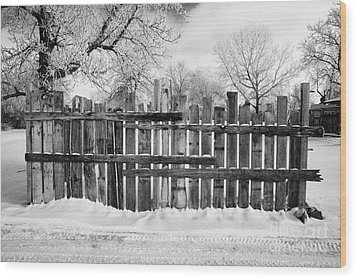 old patched up wooden fence using old bits of wood in snow Forget Saskatchewan  Wood Print by Joe Fox
