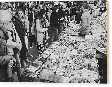 people buying chocolates on display inside the la boqueria market in Barcelona Catalonia Spain Wood Print by Joe Fox