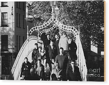 People Crossing The Hapenny Ha Penny Bridge Over The River Liffey In Dublin At A Busy Time Wood Print by Joe Fox