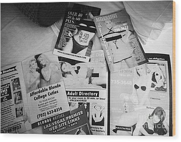 selection of leaflets advertising girls laid out on a hotel bed in Las Vegas Nevada USA Wood Print by Joe Fox