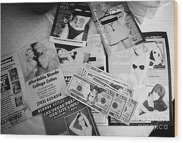 selection of leaflets advertising girls laid out on a hotel bed with us dollars cash in Las Vegas Ne Wood Print by Joe Fox