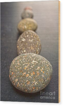 Straight Line Of Speckled Grey Pebbles On Dark Background Wood Print by Colin and Linda McKie