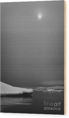 sun breaking through mist and cloud over snow covered ice shelf falling into the sea at Fournier Bay Wood Print by Joe Fox