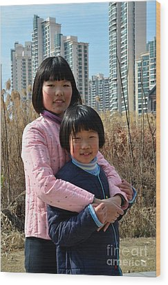 Two Chinese Teen Sisters Hug  And Embrace Shanghai China Wood Print by Imran Ahmed