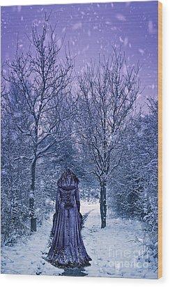 Woman Walking In Snow Wood Print by Amanda Elwell