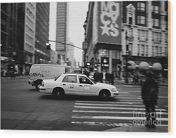 yellow cab taxi blurs past pedestrian waiting at crosswalk on Broadway outside macys new york usa Wood Print by Joe Fox